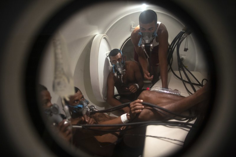 In this Feb. 7, 2018 photo, Miskito divers stricken with decompression sickness climb into a hyperbaric chamber at the hospital in Puerto Lempira, Honduras. (AP Photo/Rodrigo Abd)
