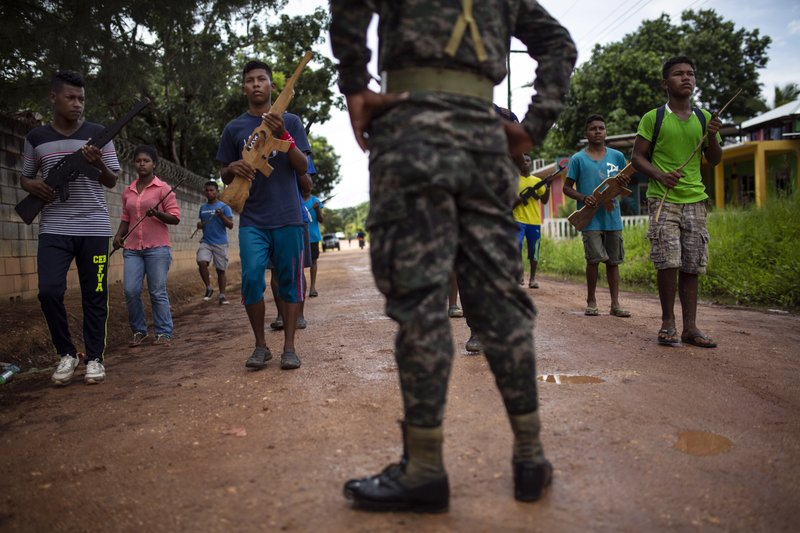 In this Sept. 5, 2018 photo, supervised by a Honduran Army soldier, students practice their routine they plan to perform in an independence military parade, in Puerto Lempira, Honduras. (AP Photo/Rodrigo Abd)