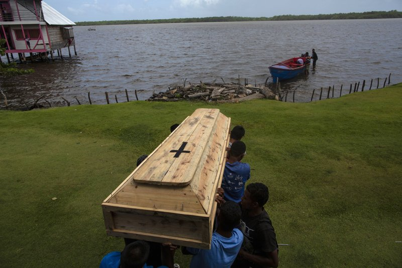 In this Sept. 2, 2018 photo, relatives and friends carry the coffin that contains the remains of Miskito diver Oscar Salomon Charly, 31, to be transported via a boat to a nearby cemetery, in Cabo Gracias a Dios, Nicaragua Charly died in Honduras after suffering a severe case of decompression sickness, (AP Photo/Rodrigo Abd)