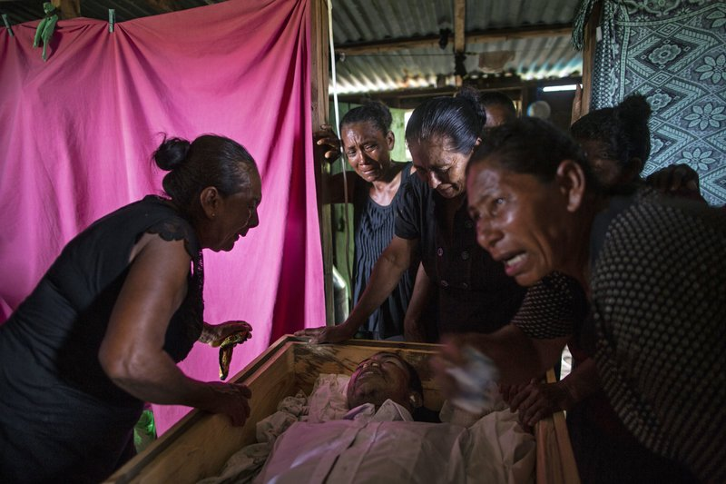 In this Sept. 2, 2018 photo, Sonia Wills, left, accompanied by relatives, mourns over the coffin that contains the remains of her 31-year-old son Miskito diver Oscar Salomon Charly, during a wake in her home in Cabo Gracias a Dios, Nicaragua. (AP Photo/Rodrigo Abd)