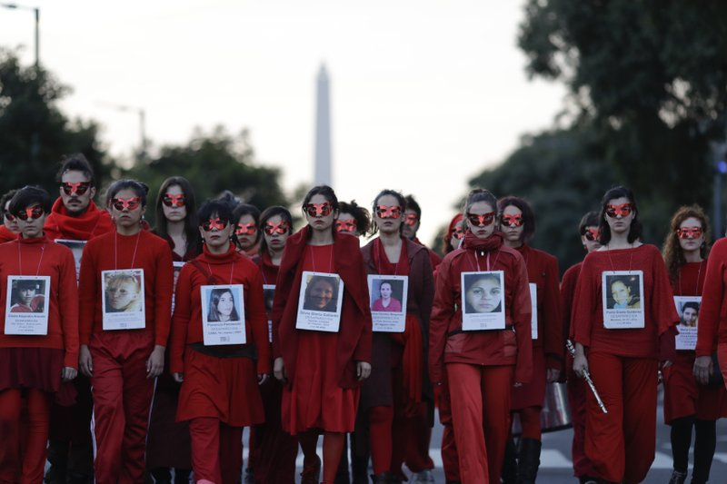 FILE - In this June 3, 2017 file photo, women hold pictures of victims of gender violence during a protest in Buenos Aires, Argentina. (AP Photo/Natacha Pisarenko, File)