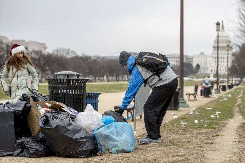 The Capitol building is visible as a man who declined to give his name picks up garbage and stacks it near a trash can during a partial government shutdown on the National Mall in Washington, Tuesday, Dec. (AP Photo/Andrew Harnik)
