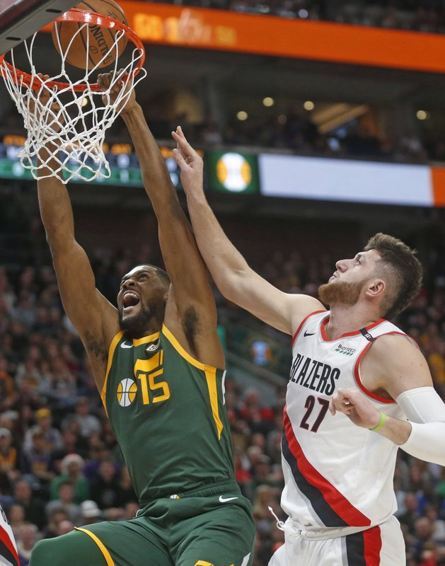Utah Jazz forward Derrick Favors (15) goes to the basket as Portland Trail Blazers center Jusuf Nurkic (27) defends during the first half of an NBA basketball game Tuesday, Dec. (AP Photo/Rick Bowmer)