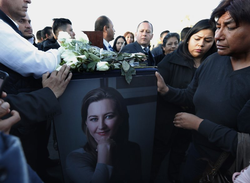 Relatives and friends surround the urn with ashes of opposition Puebla state Gov. Martha Erika Alonso during a farewell ceremony in Puebla City, southeast of Mexico, Tuesday, Dec. (AP Photo/Marco Ugarte)