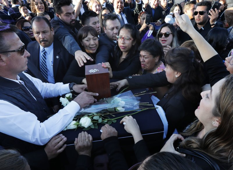 Relatives and friends touch the urn with ashes of opposition Puebla state Gov. Martha Erika Alonso during a farewell ceremony in Puebla City, southeast of Mexico, Tuesday, Dec. (AP Photo/Marco Ugarte)