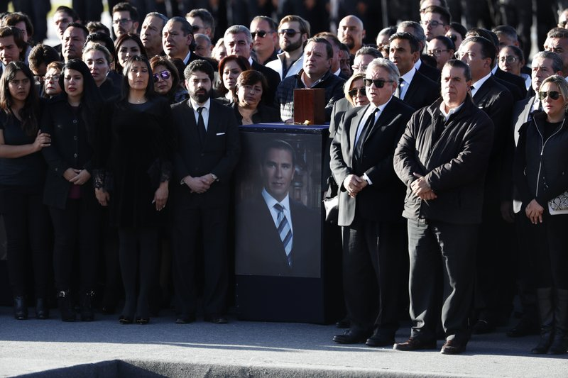 Relatives and friends stand next to an urn with ashes of Puebla state's ex-Gov. Rafael Moreno Valle, during a farewell ceremony in Puebla City, southeast of Mexico, Tuesday, Dec. (AP Photo/Marco Ugarte)