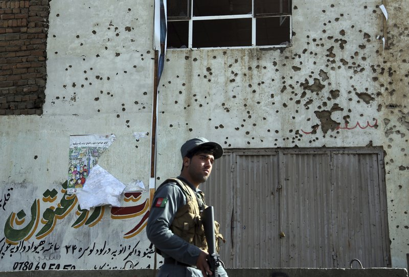 FILE - In this Oct. 29, 2018 file photo, an Afghan security personnel inspects the site of suicide attack near the election commission office in Kabul, Afghanistan. (AP Photo/Rahmat Gul, File)