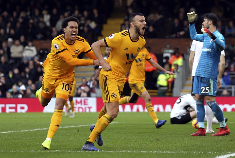 Wolverhampton Wanderers' Romain Saiss, center, celebrates scoring against Fulham during the English Premier League soccer match at Craven Cottage, London, Wednesday Dec. (Steven Paston/PA via AP)