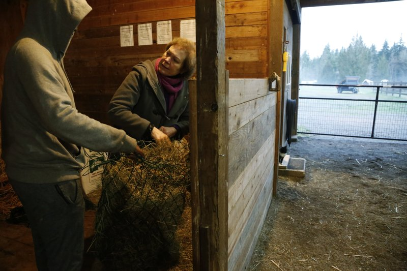 In this Monday, Dec. 10, 2018, photo, Robel, an 18-year-old tech addict from California, left, helps Hilarie Cash load hay to feed the horses at the Rise Up Ranch outside rural Carnation, Wash. (AP Photo/Martha Irvine)