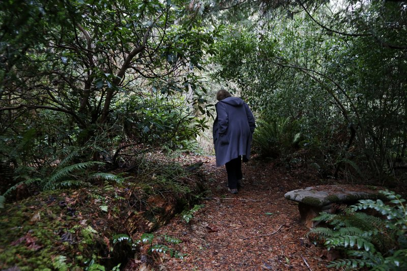 In this Monday, Dec. 10, 2018, photo, Psychologist Hilarie Cash walks on a forest path at a rehab center for adolescents in a rural area outside Redmond, Wash. (AP Photo/Martha Irvine)