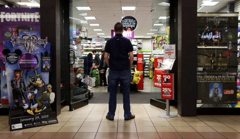 In this Dec. 9, 2018 photo, a 27-year-old self-described tech addict poses for a portrait in front of a video game store at a mall in Everett, Wash. (AP Photo/Martha Irvine)