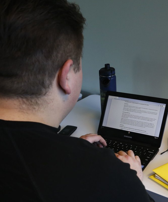 In this Monday, Dec. 10, 2018, photo, Jason, a 24-year-old tech addict from New York state, works on a laptop in Bellevue, Wash. (AP Photo/Martha Irvine)