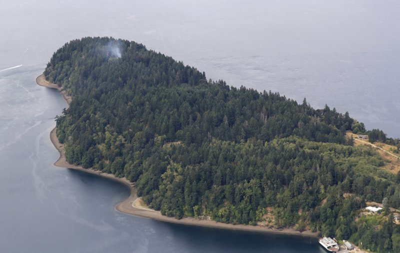 FILE - In this Aug. 11, 2018, file photo, smoke rises from the site on Ketron Island in Washington state where a Horizon Air turboprop plane crashed after it was stolen from Sea-Tac International Airport, as seen from the air near Steilacoom, Wash. (AP Photo/Ted S. Warren, File)