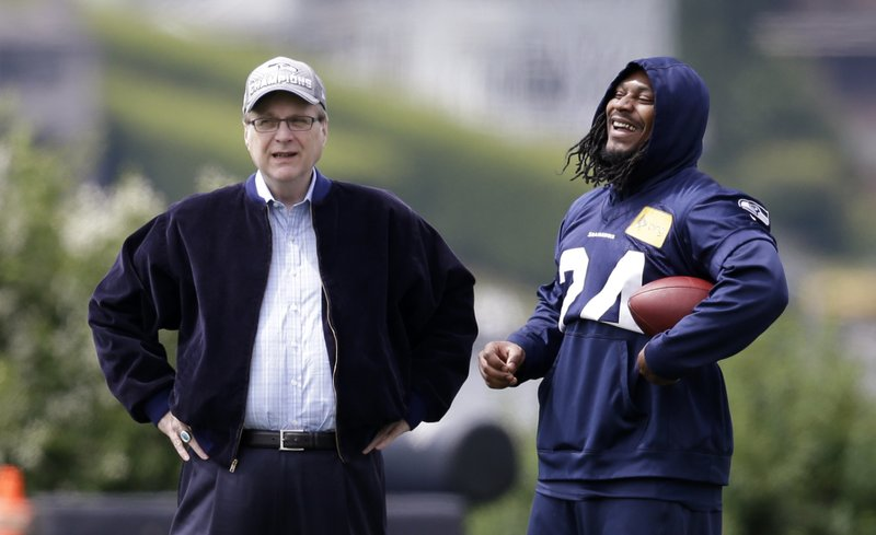 FILE - In this June 18, 2018, file photo, Seattle Seahawks owner Paul Allen, left, talks with running back Marshawn Lynch on the sidelines at an NFL football minicamp practice in Renton, Wash. (AP Photo/Elaine Thompson, File)