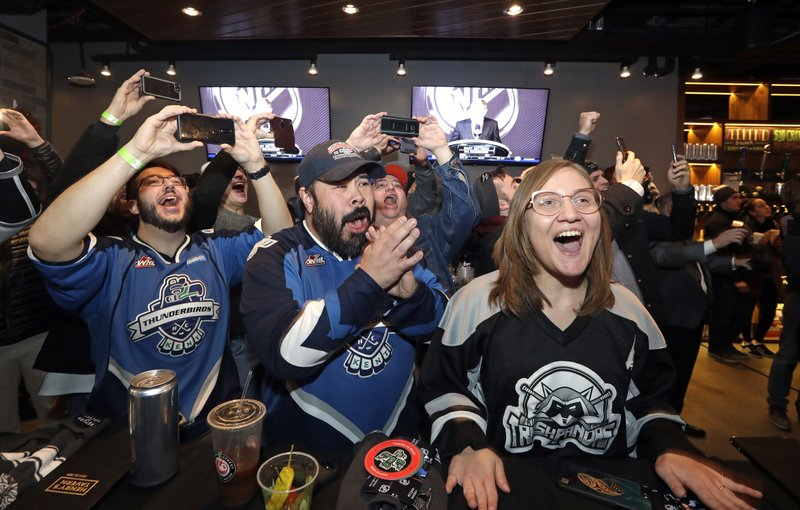 FILE - In this Dec. 4, 2018, file photo, Ryan Kelly, left, Otto Rogers and Rebecca Moloney cheer the announcement of a new NHL hockey team in Seattle at a celebratory party in Seattle. (AP Photo/Elaine Thompson, File)