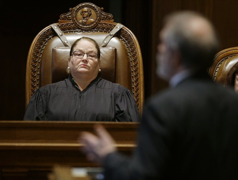 FILE - In this Oct. 24, 2017, file photo, Washington state Supreme Court Chief Justice Mary Fairhurst, left, listens as Alan Copsey, right, deputy solicitor general in the Washington state attorney general's office, speaks during a Washington Supreme Court hearing in Olympia, Wash. (AP Photo/Ted S. Warren, File)