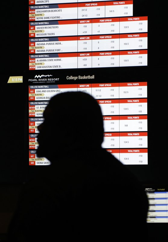 In this Dec. 18, 2018 photo, a person walks by a betting wall at the Pearl River Resort in Philadelphia, Miss. (AP Photo/Rogelio V. Solis)