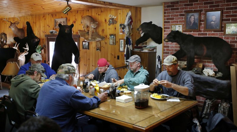 FILE - In this Sept. 19, 2014, file photo, bear hunters eat a meal at the Stony Brook Outfitters lodge in Wilton, Maine. (AP Photo/Robert F. Bukaty, File)