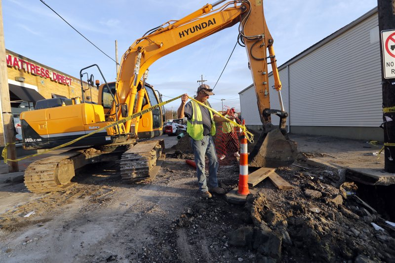 FILE - In this Jan. 31, 2018, file photo, workers fix a sewer main below the sidewalk in Mid City New Orleans. (AP Photo/Gerald Herbert, File)