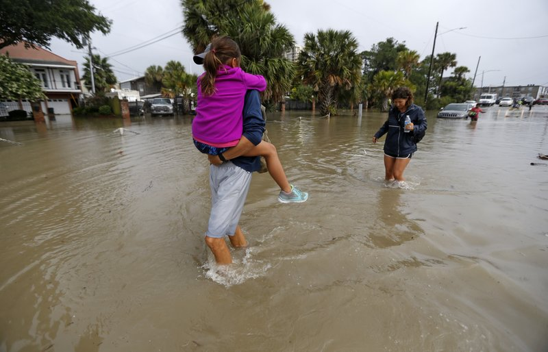 FILE - In this June 21, 2017 file photo, Don Noel carries his daughter Alexis, 8, with his wife Lauren, right as they walk through a flooded roadway to check on their boat in the West End section of New Orleans. (AP Photo/Gerald Herbert, File)