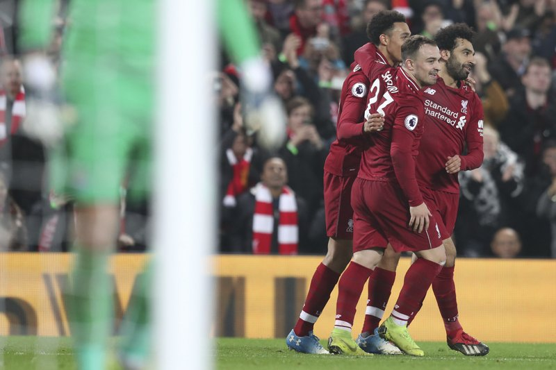 Liverpool's Xherdan Shaqiri, center, celebrates with teammates Mohamed Salah, right, after scoring his side's third goal during the English Premier League soccer match between Liverpool and Newcastle at Anfield Stadium, Liverpool, England, Wednesday, Dec. (AP Photo/Jon Super)