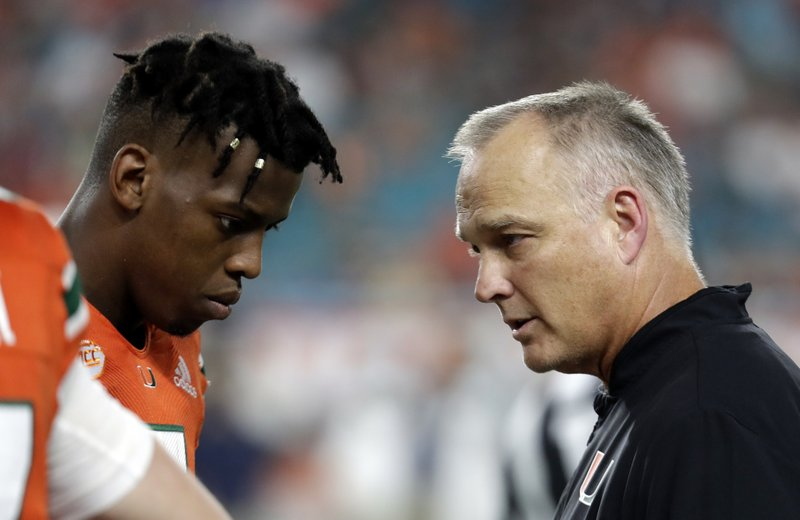 File-This Nov. 24, 2018, file photo shows Miami quarterback N'Kosi Perry, left, talking with Miami head coach Mark Richt during the second half of an NCAA college football game against Pittsburgh, in Miami Gardens, Fla. (1,089 yards passing, 13 touchdowns) a Pinstripe start. Malik Rosier, who started six games this season before he was replaced by Perry, will likely get the start. Jarren Williams could also get some snaps for the Hurricanes. Richt had not announced a starter on Wednesday. (AP Photo/Lynne Sladky, File)