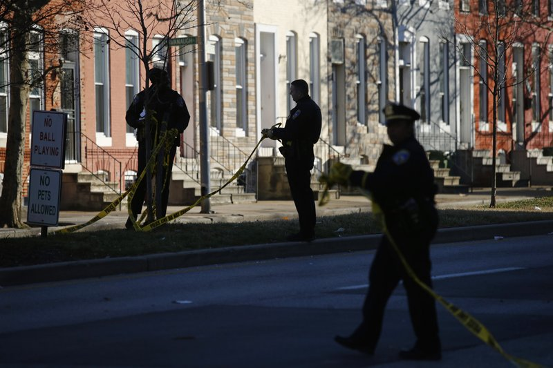 In this Dec. 19, 2018 photo, members of the Baltimore Police Department collect crime scene tape after investigating a shooting scene in Baltimore. (AP Photo/Patrick Semansky)