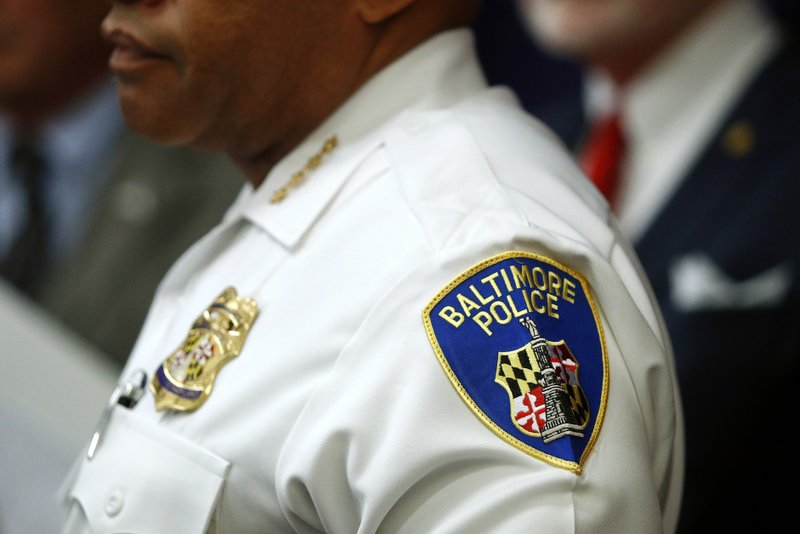 FILE - In this Aug. 29, 2018 file photo, a patch depicting the Baltimore Police Department seal is seen on Interim Commissioner Gary Tuggle's uniform as he speaks at a news conference in Baltimore. (AP Photo/Patrick Semansky, File)
