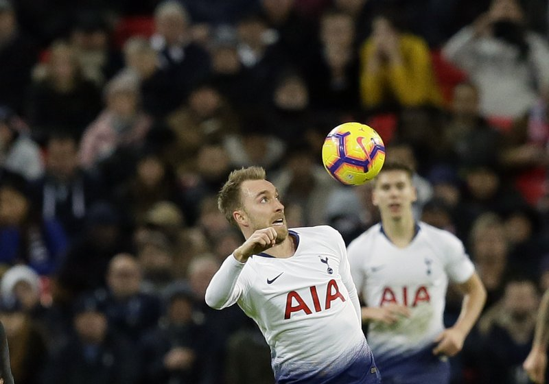 Tottenham's Christian Eriksen, center, jumps for the ball during the English Premier League soccer match between Tottenham Hotspur and Bournemouth at Wembley stadium in London, Wednesday, Dec. (AP Photo/Tim Ireland)