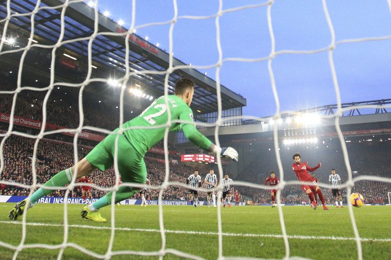 Liverpool'sMohamed Salah, right, scores on a penalty kick during the English Premier League soccer match between Liverpool and Newcastle at Anfield Stadium, Liverpool, England, Wednesday, Dec. (AP Photo/Jon Super)