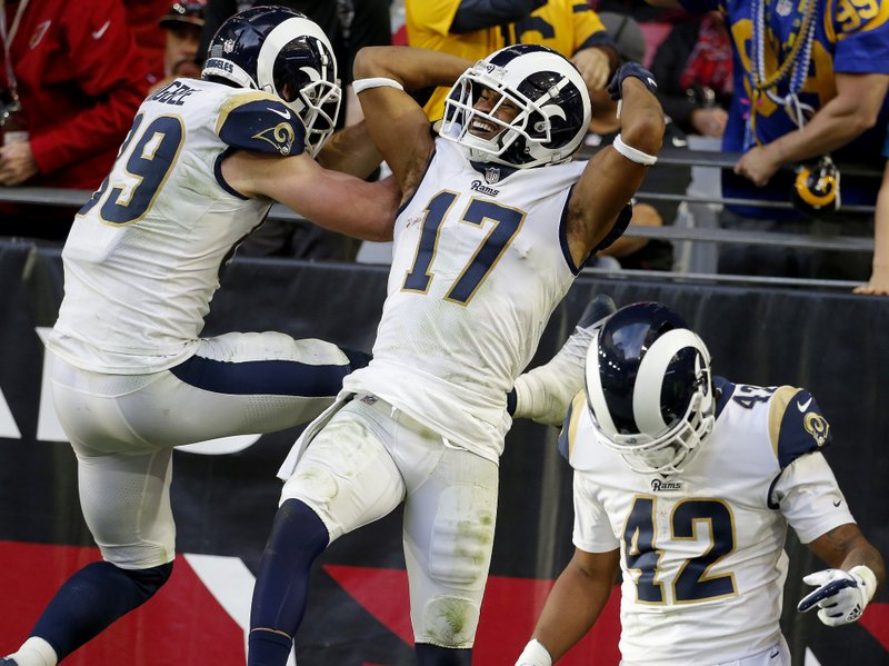 Los Angeles Rams wide receiver Robert Woods (17) celebrates his touchdown with teammates Tyler Higbee (89) and John Kelly (42) during the second half of an NFL football game against the Arizona Cardinals, Sunday, Dec. (AP Photo/Rick Scuteri)
