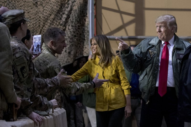 President Donald Trump and first lady Melania Trump greet members of the military at a hanger rally at Al Asad Air Base, Iraq, Wednesday, Dec. (AP Photo/Andrew Harnik)