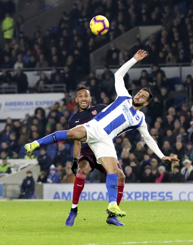 Arsenal's Pierre-Emerick Aubameyang, rear, and Brighton & Hove Albion's Martin Montoya battle for the ball during the English Premier League soccer match at the AMEX Stadium, Brighton, Wednesday Dec. (Gareth Fuller/PA via AP)