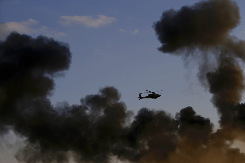 An Israeli Air Force Apache attack helicopter flies during a graduation ceremony for new pilots in the Hatzerim air force base near the city of Beersheba, Israel, Wednesday, Dec. (AP Photo/Ariel Schalit)