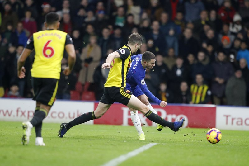 Chelsea's Eden Hazard, back shots the ball past Watford's Craig Cathcart, center during the English Premier League soccer match between Watford and Chelsea at Vicarage Road stadium in Watford, England on Wednesday, Dec. (AP Photo/Frank Augstein)