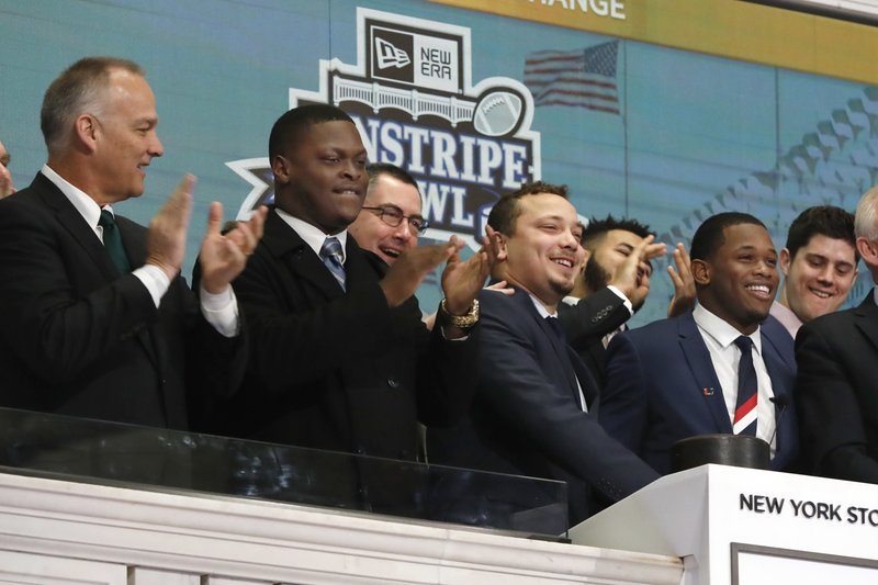University of Wisconsin football Team Captain Alec Ingold, second from right, and University of Miami football Team Captain Jaquan Johnson, right, ring the New York Stock Exchange opening bell, Wednesday, Dec. (AP Photo/Richard Drew)