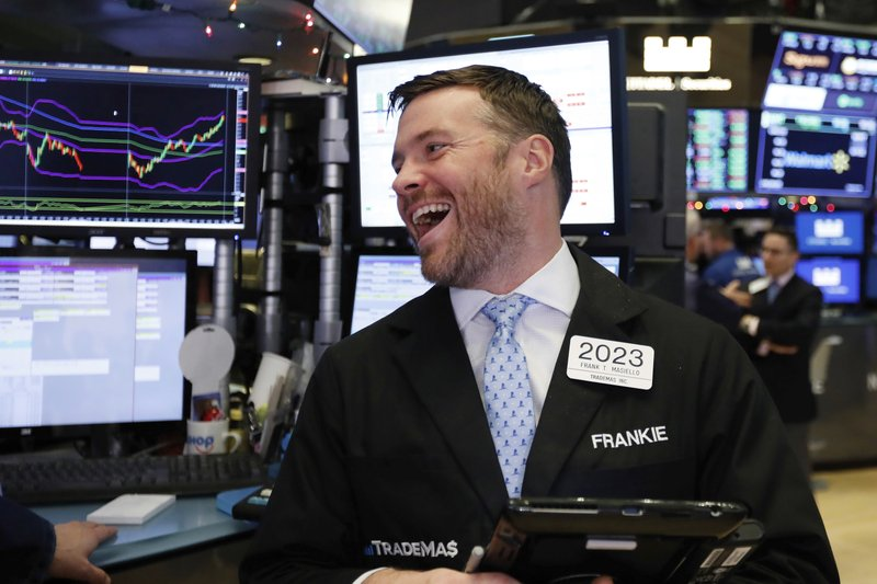 Trader Frank Masiello smiles as he works on the floor of the New York Stock Exchange before the closing bell, Wednesday, Dec. (AP Photo/Richard Drew)