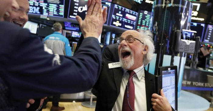 Traders Peter Tuchman, right, slaps a high five before the closing bell on the floor of the New York Stock Exchange, Wednesday, Dec. (AP Photo/Richard Drew)