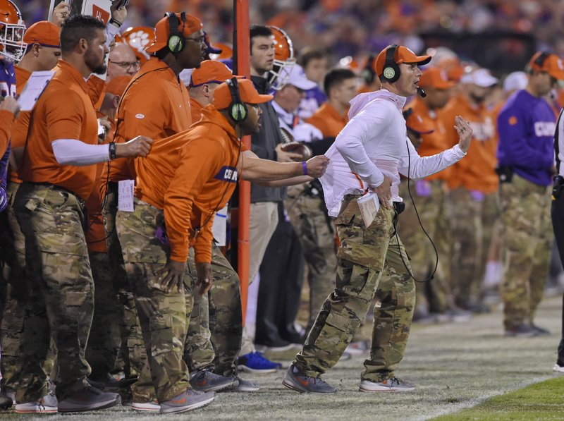File-This Nov. 17, 2018, file photo shows, Clemson defensive coach Brent Venables being pulled back by an assistant during the first half of an NCAA college football game in Clemson, S. (AP Photo/Richard Shiro, File)