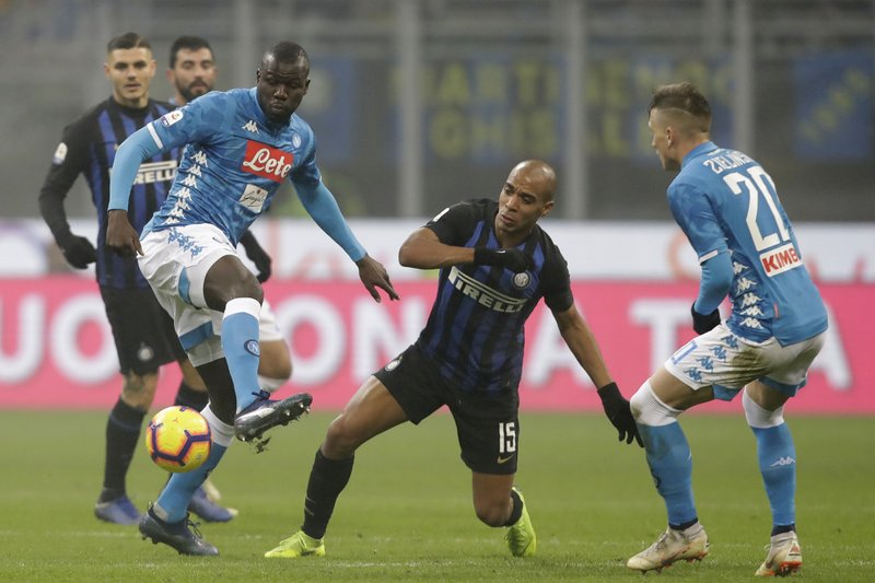 Napoli's Kalidou Koulibaly , left, fights for the ball with Inter Milan's Joao Mario, center during a Serie A soccer match between Inter Milan and Napoli, at the San Siro stadium in Milan, Italy, Wednesday, Dec. (AP Photo/Luca Bruno)