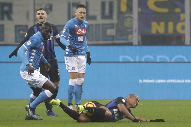 Inter Milan's Joao Mario, right, is fouled by Napoli's Kalidou Koulibaly during a Serie A soccer match between Inter Milan and Napoli, at the San Siro stadium in Milan, Italy, Wednesday, Dec. (AP Photo/Luca Bruno)