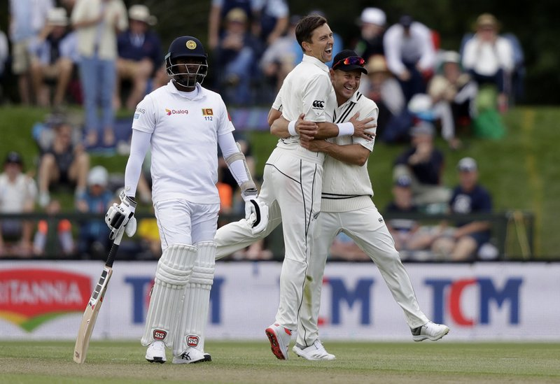 New Zealand's Trent Boult is congratulated by teammate Neil Wager, right, after taking the wicket of Sri Lanka's Lahiru Kumara during play on day two of the second cricket test between New Zealand and Sri Lanka at Hagley Oval in Christchurch, New Zealand, Thursday, Dec. (AP Photo/Mark Baker)
