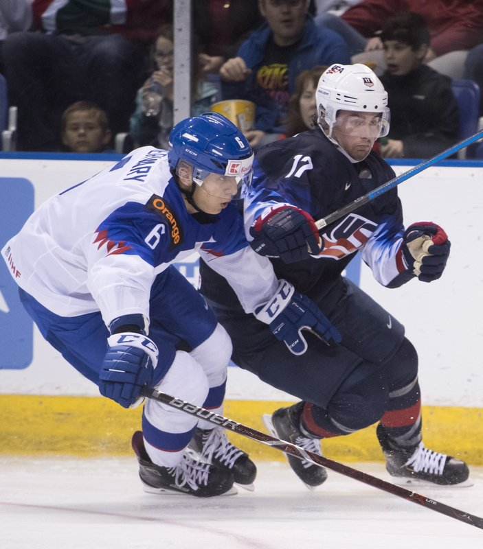United States' Evan Barratt, right, fights for control of the puck with Slovakia's Martin Fehervary during the second period in a world junior men's hockey championship game in Vancouver, British Columbia, Wednesday, Dec. (Jonathan Hayward/The Canadian Press via AP)