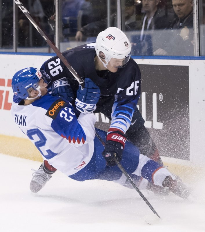 CORRECTS CITY TO VICTORIA, INSTEAD OF VANCOUVER - United States' Mikey Anderson, right, fights for control for the puck with Slovakia's Adam Ziak during the first period in a world junior men's hockey championship game in Victoria, British Columbia, Wednesday, Dec. (Jonathan Hayward/The Canadian Press via AP)