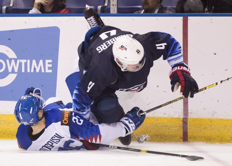 CORRECTS CITY TO VICTORIA, INSTEAD OF VANCOUVER - United States' Dylan Samberg fights for control of the puck with Slovakia's Martin Pospisil, left, during the first period in a world junior men's hockey championship game in Victoria, British Columbia, Wednesday, Dec. (Jonathan Hayward/The Canadian Press via AP)