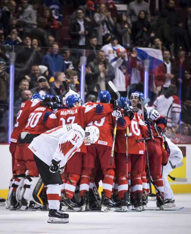 Switzerland's Yannick Bruschweiler (10) skates past as Czech Republic players celebrate their overtime win in a world junior men's hockey championship game in Vancouver, British Columbia, Wednesday, Dec. (Darryl Dyck/The Canadian Press via AP)
