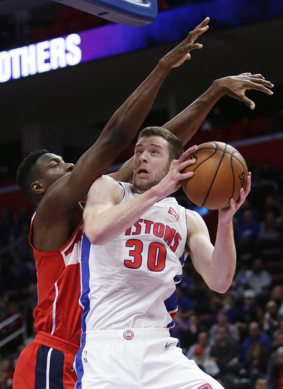Detroit Pistons forward Jon Leuer (30) goes to the basket against Washington Wizards center Ian Mahinmi, left, during the first half of an NBA basketball game Wednesday, Dec. (AP Photo/Duane Burleson)
