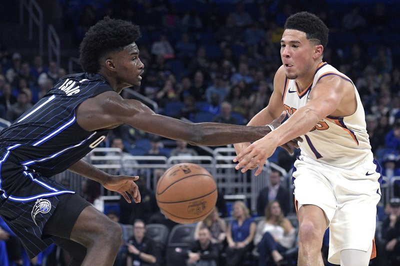 Phoenix Suns guard Devin Booker (1), right, passes the ball in front of Orlando Magic forward Jonathan Isaac (1) during the first half of an NBA basketball game Wednesday, Dec. (AP Photo/Phelan M. Ebenhack)