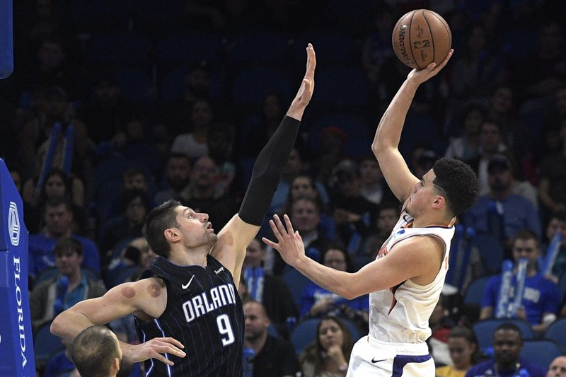 Phoenix Suns guard Devin Booker, right, goes up for a shot in front of Orlando Magic center Nikola Vucevic (9) during overtime of an NBA basketball game Wednesday, Dec. (AP Photo/Phelan M. Ebenhack)