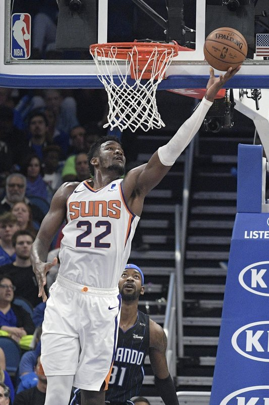 Phoenix Suns center Deandre Ayton (22) goes up for a shot in front of Orlando Magic guard Terrence Ross (31) during the second half of an NBA basketball game Wednesday, Dec. (AP Photo/Phelan M. Ebenhack)